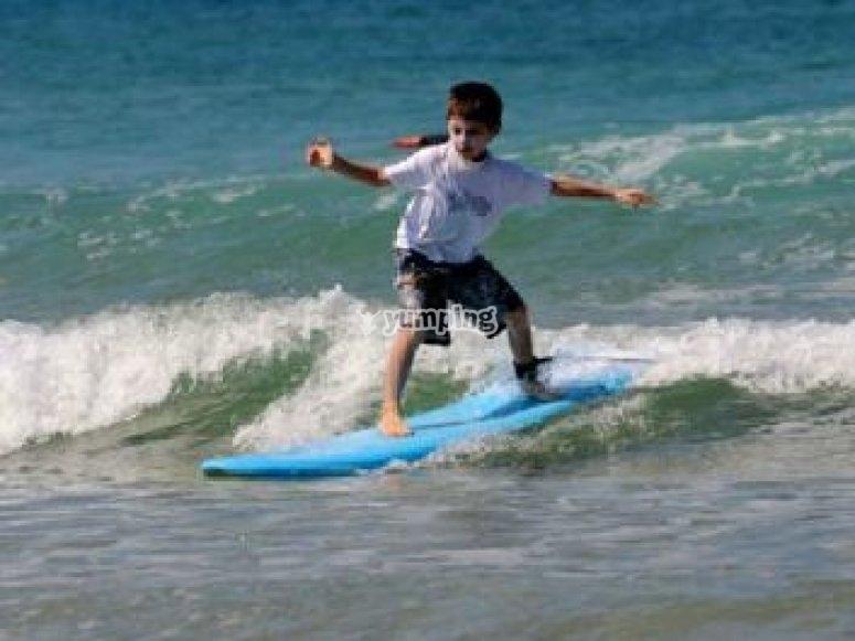 Cours de surf enfant sur une planche en mousse