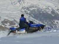 Suivez le moniteur de motoneige dans la montagne